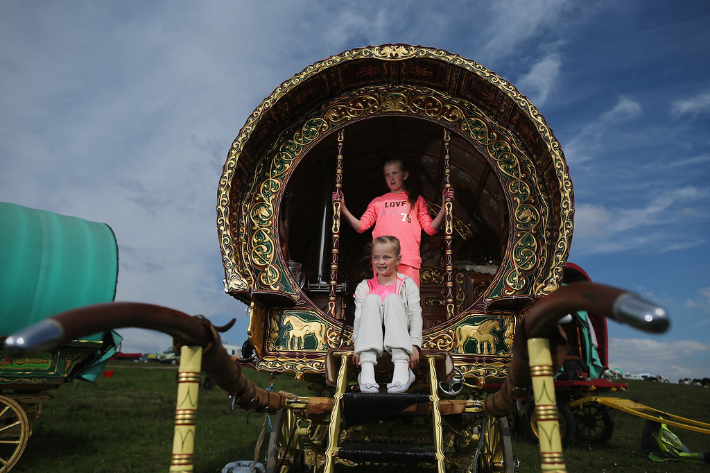 . Traveling sisters Laila Gaskin, aged 11, and Mia 10, watch horses being paraded through Appleby during the Appleby Horse Fair on June 4, 2015 in Appleby, England. The Appleby Horse Fair has existed under the protection of a charter granted by James II since 1685 and is one of the key gathering points for the Romany, gypsy and traveling community. The fair is attended by about 5,000 travelers who come to buy and sell horses. The animals are washed and groomed before being ridden at high speed along the \'mad mile\' for the viewing of potential buyers.  (Photo by Christopher Furlong/Getty Images)