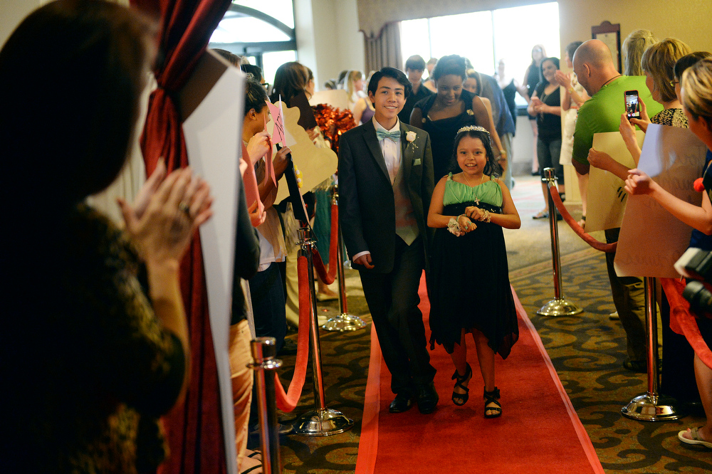 . Matt Deleon, age 14, left, escorted his cousin Amaya Martinez, age 14, right, on the red carpet Friday night. Children\'s Hospital hosted a prom for teens that might have missed their regular prom due to medical issues. The event was held at the Double Tree Hotel Friday night, June 13, 2014. The prom provides patients to have the opportunity to experience one of the biggest rites of teen passage. (Photo by Karl Gehring/The Denver Post)