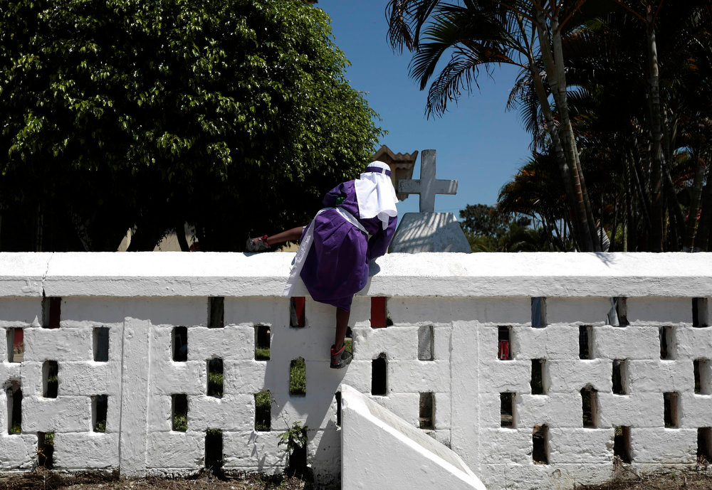 . A boy from the Garifuna ethnic people, who is participating in a re-enactment of the crucifixion of Jesus Christ on Good Friday during Holy Week, takes a shortcut to get back to the procession in Livingston, 350 km (217 miles) north east Guatemala City March 29, 2013. Holy Week is celebrated in many Christian traditions during the week before Easter. Garifuna are descendants of Carib and Arawak indians and West African slaves who settled along the Atlantic coast of Guatemala, Belize, Nicaragua and Honduras after the British deported them from St. Vincent in the 18th century. REUTERS/Jorge Dan Lopez