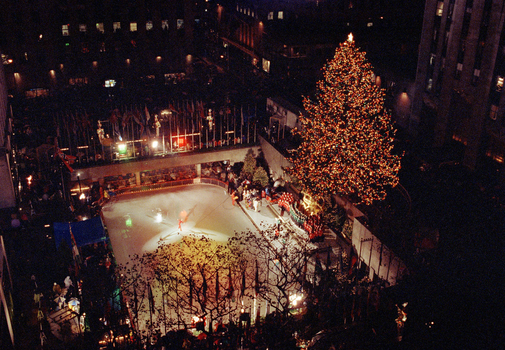. A skater performs on the ice under a lit Christmas tree in New York\'s Rockefeller Center after it was lit, Dec. 3, 1991. The 65-foot Norway spruce grown in Suffern, N.Y., is decorated with over 25,000 multi-colored bulbs. The tree will be lit daily until Jan. 7. (AP Photo/Ed Bailey)