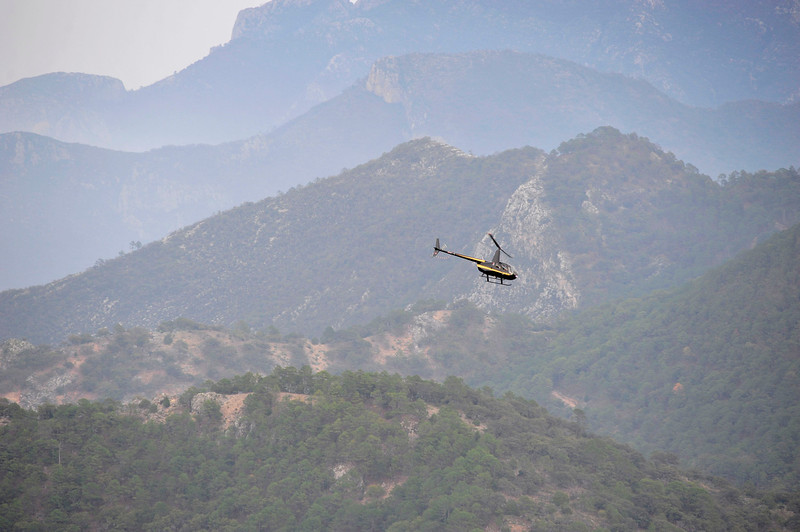 . A helicopter flies over a crash site in the municipality of Iturbide, south of Monterrey December 9, 2012. Mexican-American singer Jenni Rivera died in a plane crash after the small jet she was travelling in went down in northern Mexico, her father said on Sunday. Investigators are still searching the crash site and the transportation and communications ministry said the wreckage was strewn so far and wide that it was hard to recognize anything.  REUTERS/Stringer