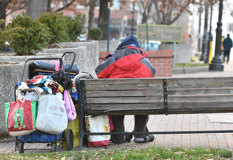 A woman sits with her belongings a City Market Park (Dec. 18, 2020)