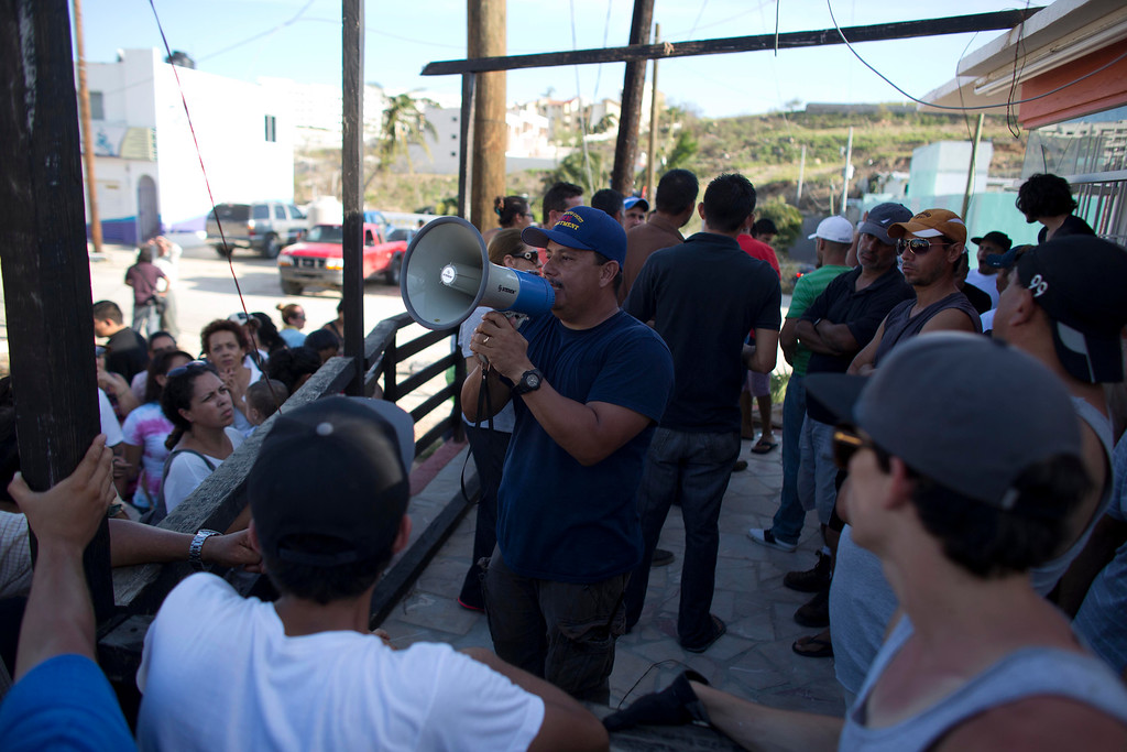 . A man uses a bullhorn to call on residents to prepare themselves against looters and criminal gangs after the passing of Hurricane Odile in San Jose de los Cabos, Mexico, Wednesday, Sept. 17, 2014. Federal police on Thursday vowed to crack down on lawlessness and restore order in the hurricane-stricken resort area. There were reports of gunfire overnight, and residents in Los Cabos lit large bonfires to try to protect their neighborhoods as they faced a fourth day without power or running water following the blow from Hurricane Odile. (AP Photo/Dario Lopez-Mills)