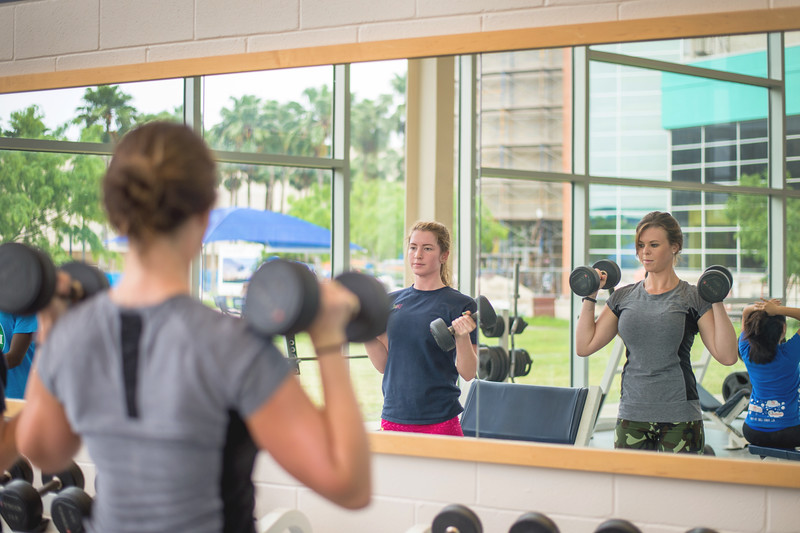 Tabitha Hinojosa(left) and Michelle Holland work together as partners in their strength & conditioning for women class in the Dugan Wellness Center.