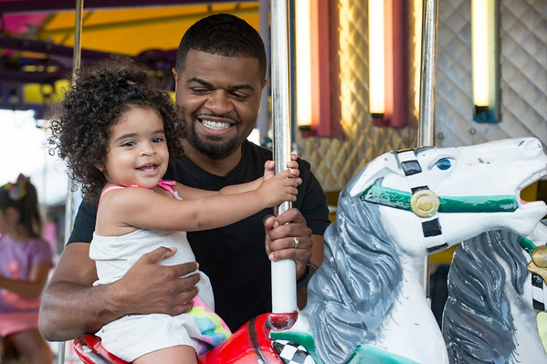 07/12/19 Wesley Bunnell | Staff Torrence Conaway holds his daughter Liv Caly Conaway, age 1, as she is all smiles on a ride at the Holy Cross Bazaar on Friday July 12, 2019.