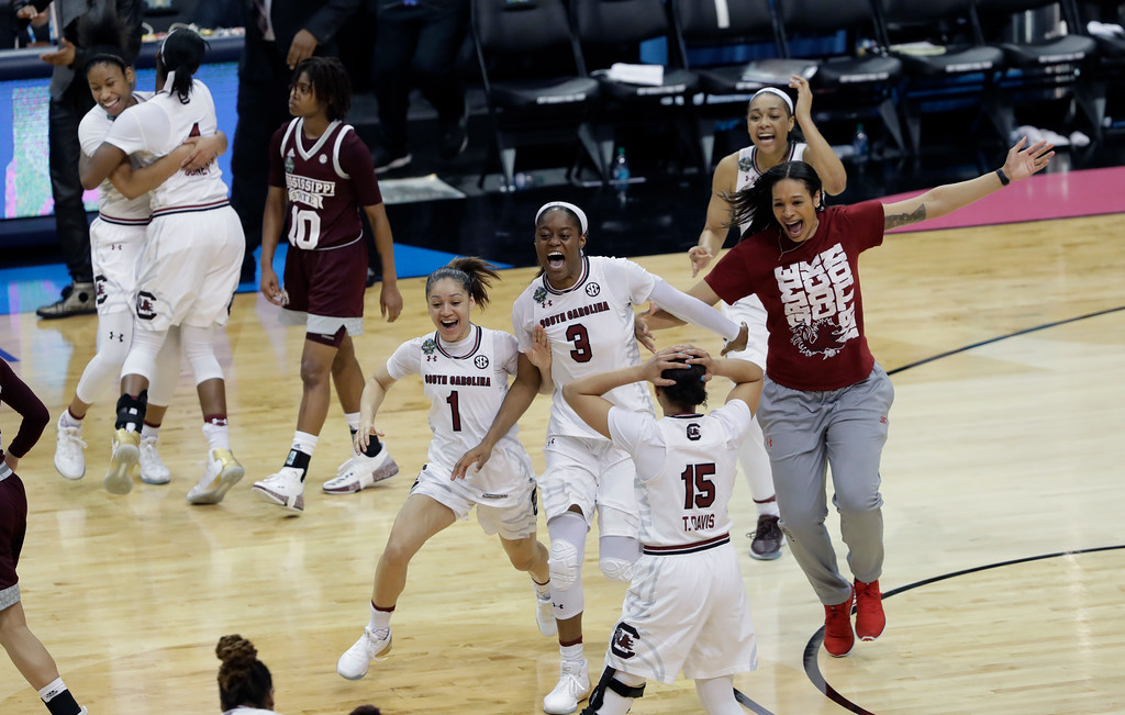 . South Carolina guard Bianca Cuevas-Moore (1) and guard Kaela Davis (3) celebrate with teammates after their win over Mississippi State in the final of the NCAA women\'s Final Four college basketball tournament, Sunday, April 2, 2017, in Dallas. South Carolina won 67-55. (AP Photo/Eric Gay)