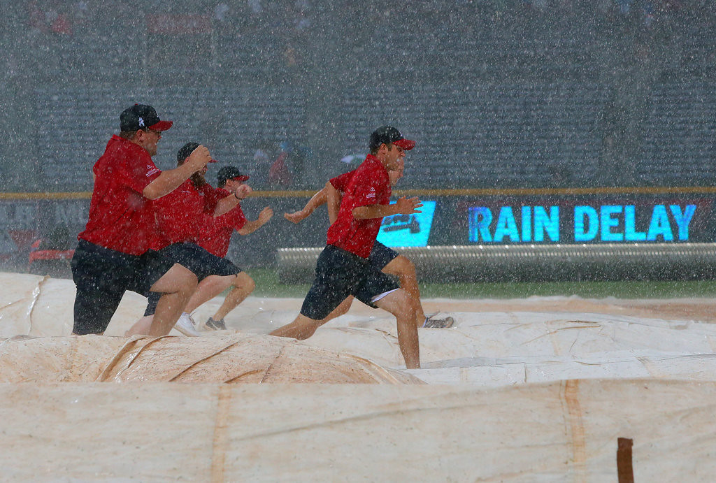 . The grounds crew scrambles to cover the infield during a rain delay. (Curtis Compton/Atlanta Journal-Constitution/MCT)