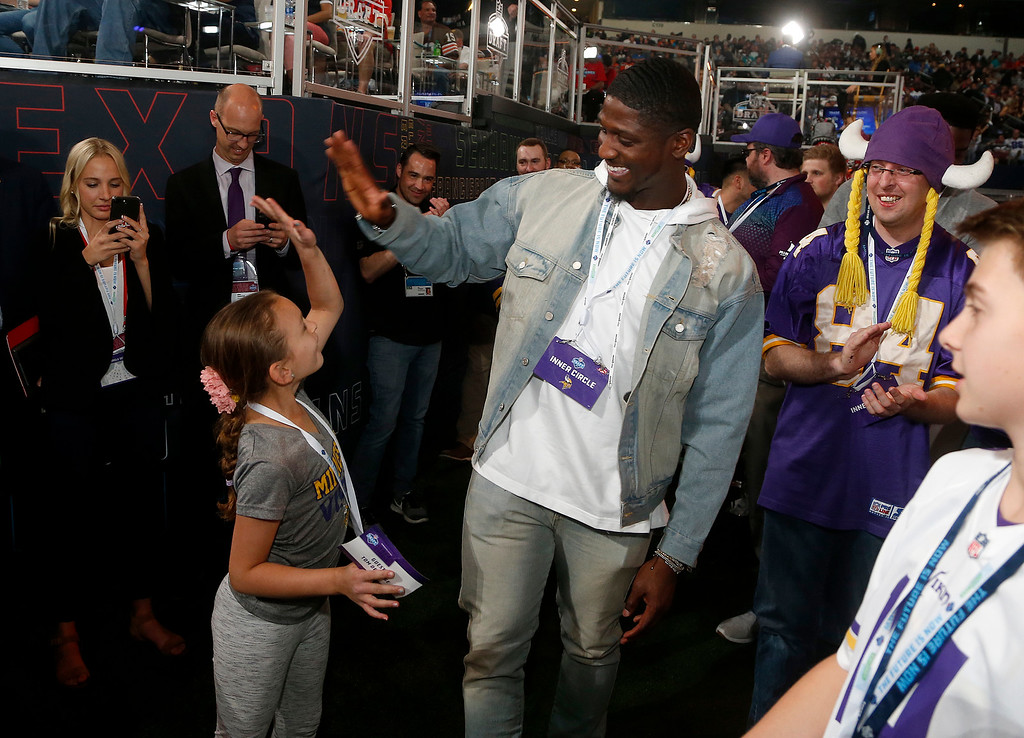 . Minnesota Vikings\' Xavier Rhodes celebrates with fan Ciana Devange of Trophy Club, Texas, as they watch the first round of the NFL football draft, Thursday, April 26, 2018, in Arlington, Texas. (AP Photo/Michael Ainsworth)