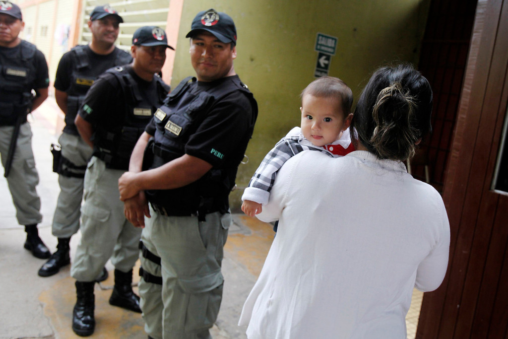 . An inmate holding her baby walks next to prison guards during celebrations for Mother\'s Day at Santa Monica female prison in Lima, May 10, 2013. New nursery facilities for the inmates\' babies were inaugurated by Peru\'s prison authorities to improve the care and education of 40 children that are permitted to stay with their mothers in the prison till they are three-years-old. REUTERS/Enrique Castro-Mendivil