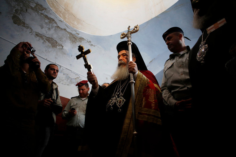 . Greek Patriarch Metropolitan Theophilos (C) holds a cross during a ceremony at the baptismal site known as Qasr el-Yahud on the banks of the Jordan River near the West Bank city of Jericho January 18, 2013. Over a thousand Orthodox Christians flocked to the Jordan River to celebrate the feast of the Epiphany at the traditional site where it is believed John the Baptist baptised Jesus. REUTERS/Baz Ratner