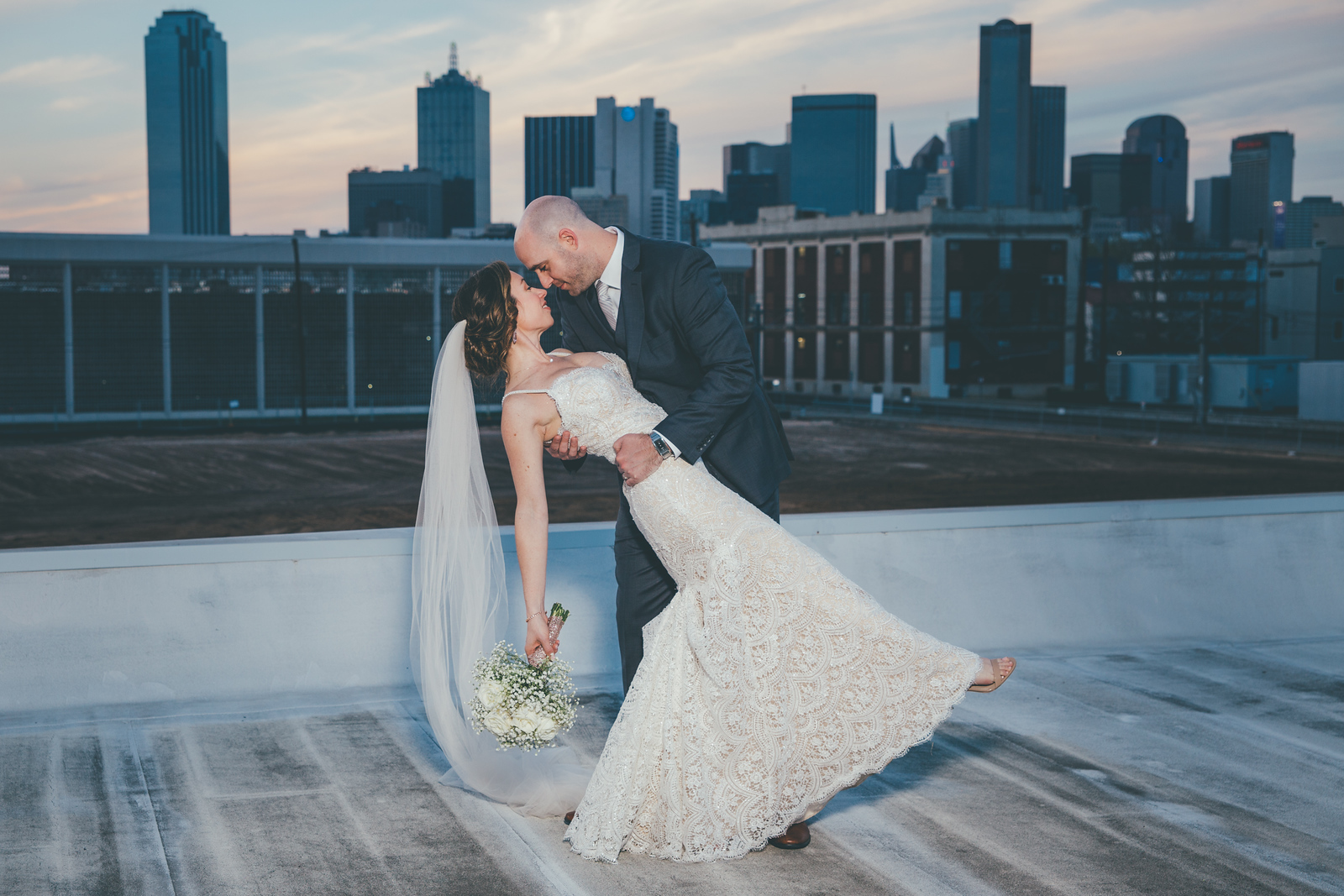 a groom dipping his bride at sunset with the downtown dallas skyline behind them