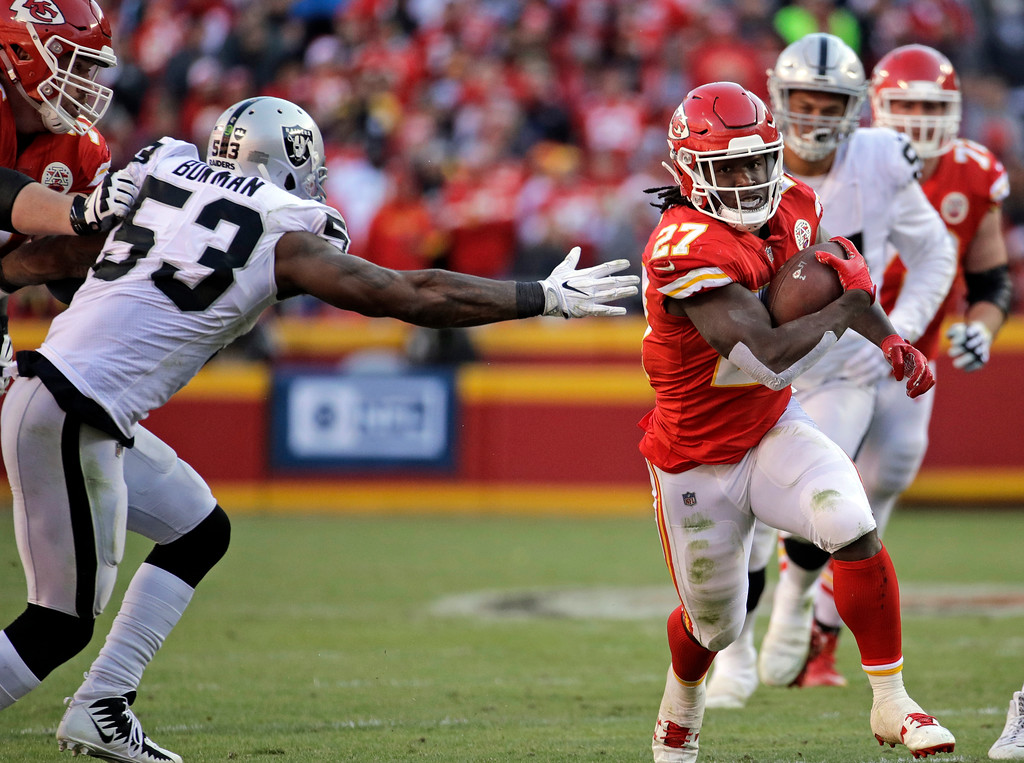 . Kansas City Chiefs running back Kareem Hunt (27) carries the ball away from Oakland Raiders linebacker NaVorro Bowman (53) during the second half of an NFL football game in Kansas City, Mo., Sunday, Dec. 10, 2017. (AP Photo/Charlie Riedel)
