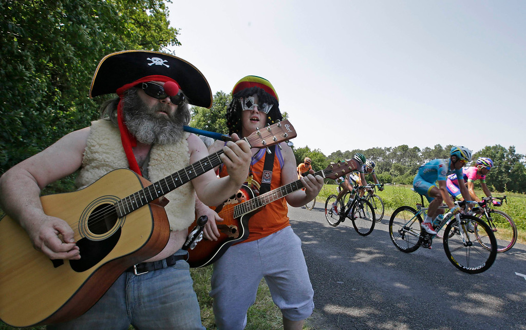 . Spectators playing guitar pose as a group of riders cycles cycles on its way during the twelfth 218km stage of the centenary Tour de France cycling race from Fougeres to Tours July 11, 2013.     REUTERS/Jacky Naegelen