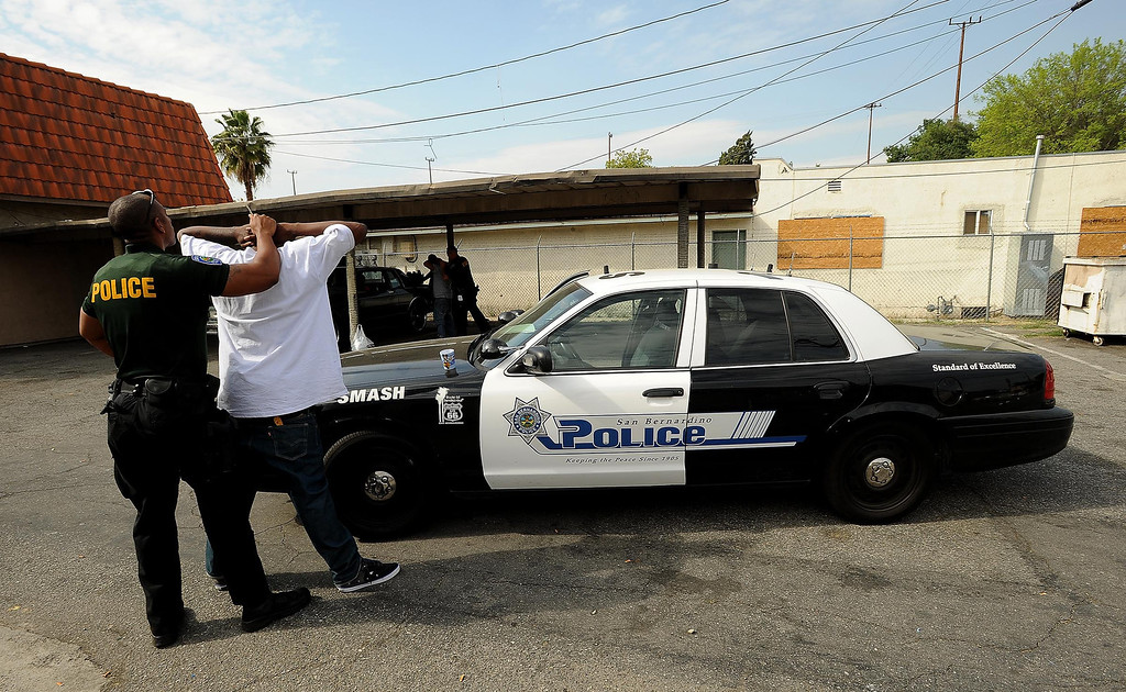 . An unidentified man is detained during a SMASH sweep along the 1200 block of N. Genevieve Street in San Bernardino April 4, 2013.   GABRIEL LUIS ACOSTA/STAFF PHOTOGRAPHER.