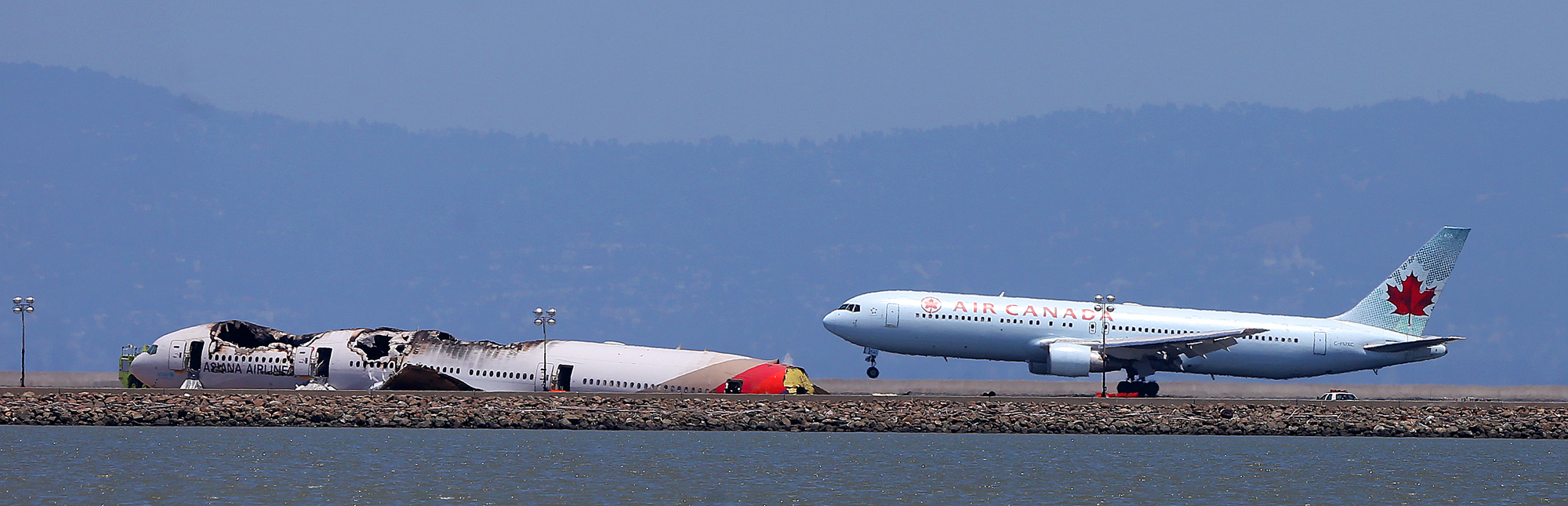 . An Air Canada jet passes the wreckage of Asiana Airlines Flight 214 as it lands at San Francisco International Airport on Sunday, July 7, 2013, in San Francisco, Calif.  Asiana Airlines Flight 214 crashed as it was landing at the airport on Saturday killing two passengers and injuring hundreds.   (Aric Crabb/Bay Area News Group)