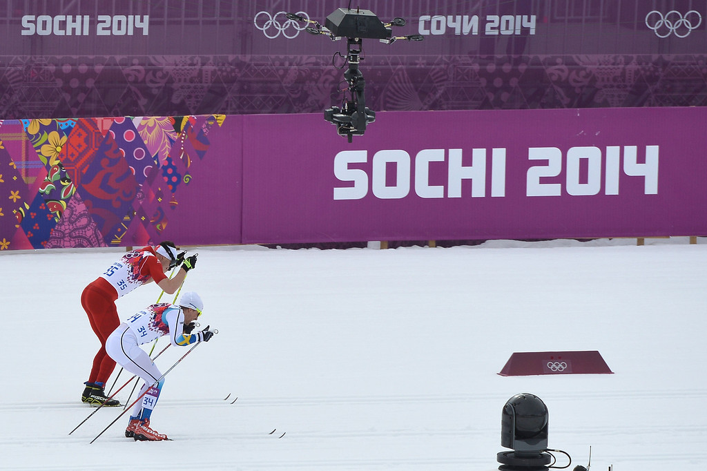 . Gold medalist Switzerland\'s Dario Cologna and silver medalist Sweden\'s Johan Olsson (34) compete in the Men\'s Cross-Country Skiing 15km Classic at the Laura Cross-Country Ski and Biathlon Center during the Sochi Winter Olympics on February 14, 2014 in Rosa Khutor near Sochi. AFP PHOTO / ALBERTO PIZZOLI/AFP/Getty Images