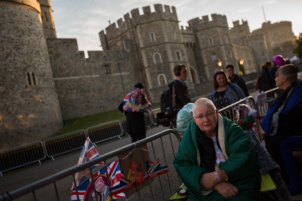 . A woman sits after spending the night in front of Windsor castle, England, Friday, May 18, 2018. Preparations continue in Windsor ahead of the royal wedding of Britain\'s Prince Harry and Meghan Markle Saturday May 19. (AP Photo/Emilio Morenatti)