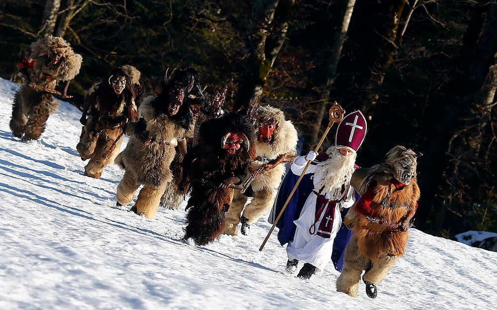 ". A man dressed as Saint Nicholas and people in traditional Bavarian attire known as ""Buttenmandl\"" and \""Krampusse\"" march in the southern German town of Maria Gern near Berchtesgaden on December 24, 2012. Buttenmandl and Krampusse consist of animal skins and masks attached to large cow-bells used to make loud, frightening noises and are worn by single young men. They follow Saint Nicholas from house to house each year to bring luck to the good and punishment for the idle.      REUTERS/Michael Dalder"