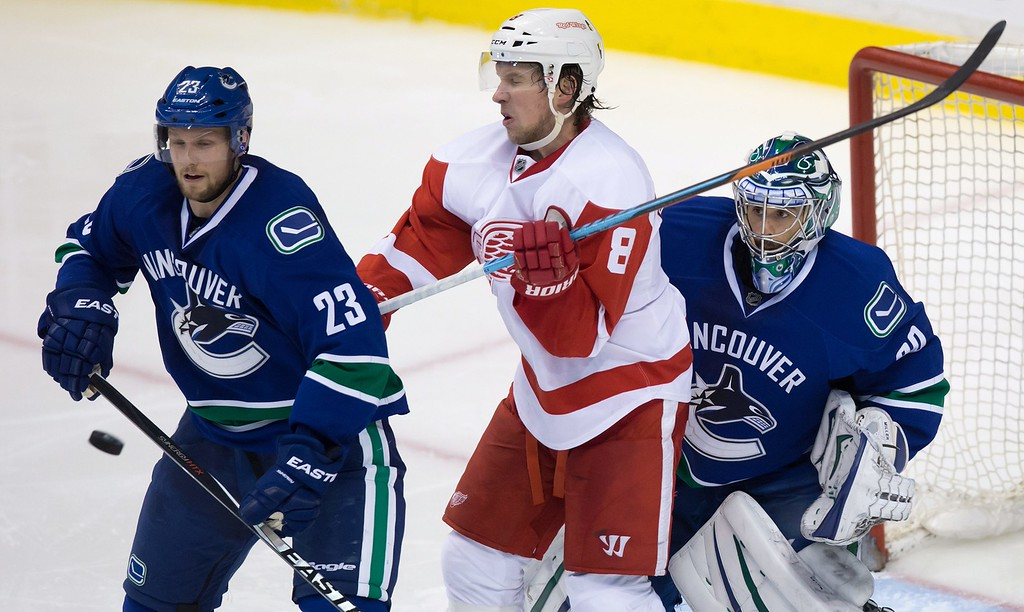 . Vancouver Canucks\' Alexander Edler (23), of Sweden, and goalie Ryan Miller, right, and Detroit Red Wings\' Justin Abdelkader (8) watch the puck after a shot from the point during the third period  of an NHL hockey game in Vancouver, British Columbia, on Saturday, Jan. 3, 2015. (AP Photo/The Canadian Press, Darryl Dyck)