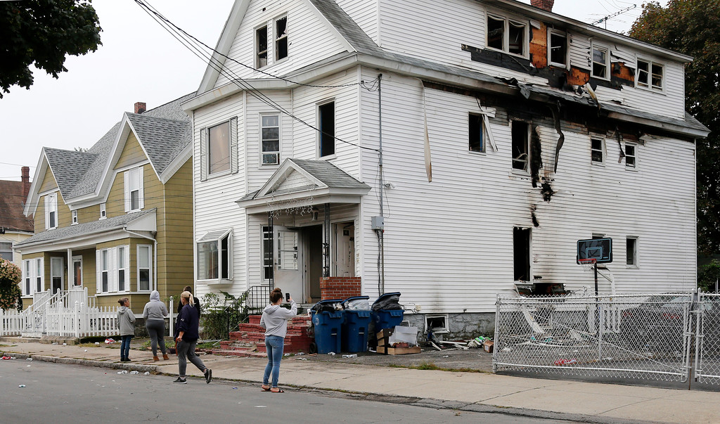 . Lawrence residents stop to take photos of a house on Bowdoin Street in Lawrence Mass., Friday, Sept. 14, 2018. The home was one of multiple houses that went up in flames on Thursday afternoon after gas explosions and fires triggered by a problem with a gas line that feeds homes in several communities north of Boston (AP Photo/Mary Schwalm)