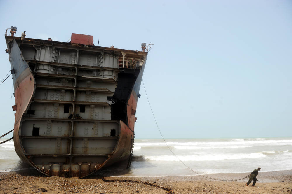 . In this photograph taken on July 10, 2012, a Pakistani worker pulls on a wire he will connect to a thick chain that will in turn be used to peel away a slab of the outer structure of a beached vessel in one of the 127 ship-breaking plots in Geddani, some 40Kms west of Karachi. Geddani\'s ship-breaking yards employ some 10,000 workers including welders, cleaners, crane operators and worker supervisors. The yards are one of the largest ship-breaking operations in the world rivaling in size those located in India and Bangladesh. It takes 50 workers about three months to break down a midsize average transport sea vessel of about 40,000 tonnes. The multimillion-dollar ship-breaking industry contributes significantly to the national supply of steel to Pakistani industries. For a six-day working week of hard and often dangerous work handling asbestos, heavy metals and polychlorinated biphenyls (PCBs), employees get paid about 300 USD a month of which half is spent on food and rent for run-down rickety shacks near the yards, a labour representative told AFP.      AFP PHOTO / Roberto  SCHMIDT/AFP/Getty Images