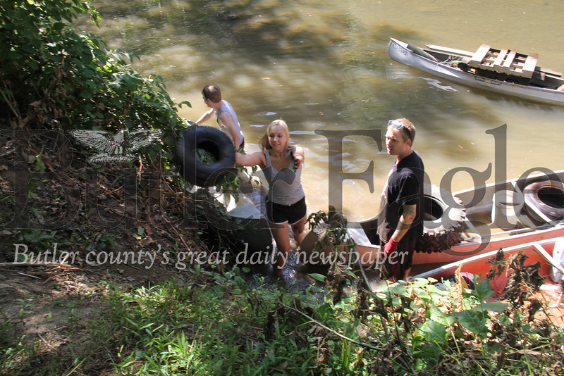 Lexi Rudolph tosses a tire to shore on Saturday during the Connoquenessing Creek cleanup.