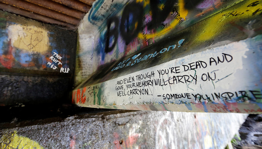 . In this photo taken Monday, Sept. 23, 2013, graffiti, mostly written about Kurt Cobain, the late frontman of Nirvana, adorns the underside of the Young Street Bridge blocks from his childhood home in Aberdeen, Wash.  (AP Photo/Elaine Thompson)