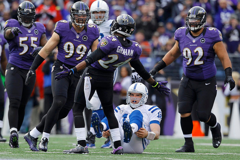. Indianapolis Colts quarterback Andrew Luck (C) sits on the field after being sacked by Baltimore Ravens cornerback Corey Graham (24) and outside linebacker Paul Kruger (99) during the first half of their NFL AFC wildcard playoff game in Baltimore January 6, 2013.  REUTERS/Gary Cameron