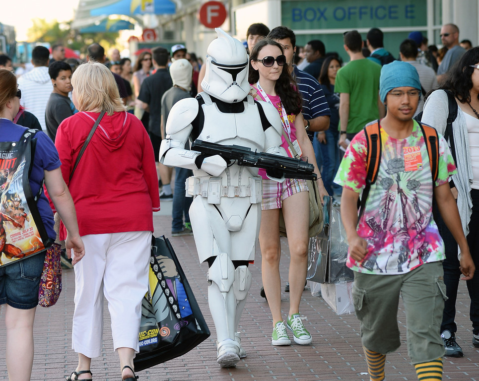". Myke Soler (C) of California walks outside the San Diego Convention Center dressed as a clone trooper from the ""Star Wars\"" movie franchise with his wife Kimberly Soler during Comic-Con International 2013 on July 17, 2013 in San Diego, California.  (Photo by Ethan Miller/Getty Images)"