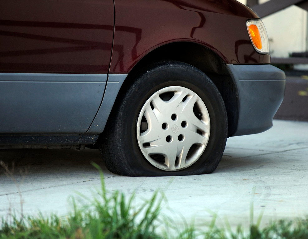. One of many flat tires is found in front of homes along Glazier Drive in Concord, Calif., on Monday, Feb. 11, 2013. Concord police officers found tires slashed on about 60 vehicles in the area over the weekend. (Susan Tripp Pollard/Staff)