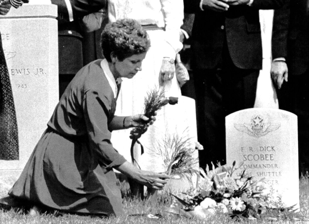 Description of . June Scobee, widow of Challenger commander Francis R. Scobee, places flowers at her husband's grave in Arlington National Cemetery on May 19, 1986.  Credit: UPI