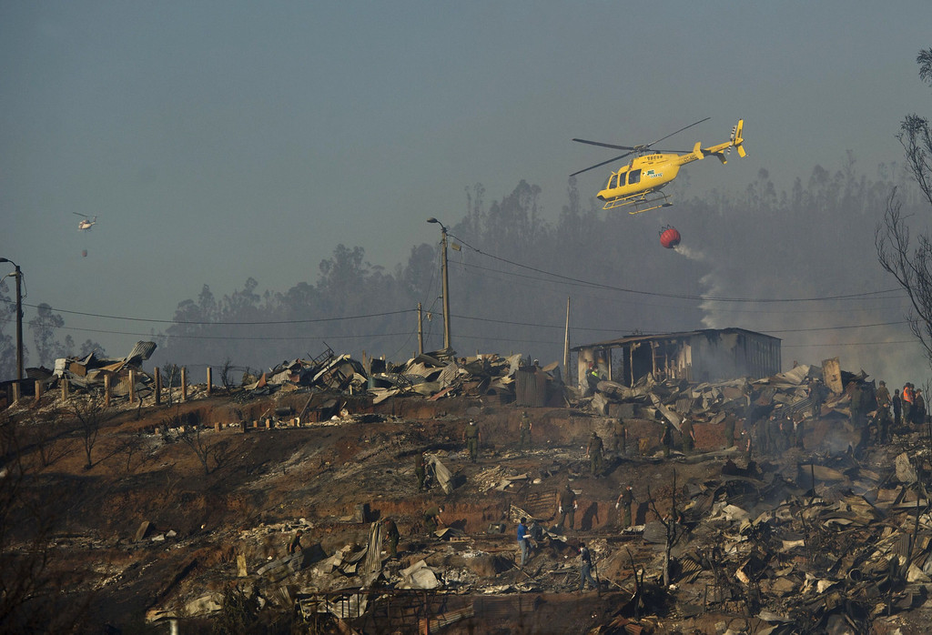 . A helicopter empties a bucket of water to fight a fire in Valparaiso, Chile, on April 14, 2014. Emergency responders struggled Monday with outbreaks from a deadly blaze that tore through parts of an historic Chilean port city, as authorities hoped to have control of the flames in two to three days.   AFP PHOTO/MARTIN BERNETTI/AFP/Getty Images
