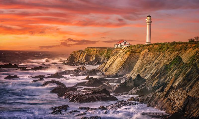 lighthouse near rocky beach with sunset