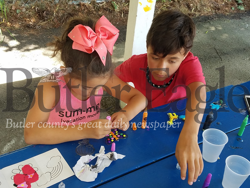Isabella Roskovski (left) and her brother, Andrew, make plastic-glass paintings at the South Hills Playground, as part of the Summer Food & Fun Program, sponsored by the Greater Pittsburgh Food Bank.