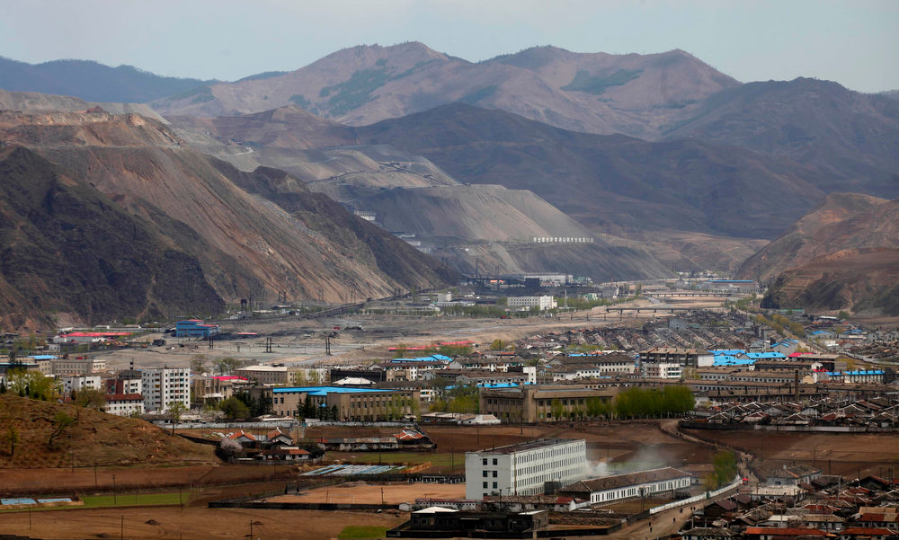 . A North Korean iron ore mine (L) is seen near the North Korean town of Musan on May 11, 2013. Chinese currency and U.S. dollars are being used more widely than ever in North Korea instead of the country\'s own money. The use of dollars and Chinese yuan, or renminbi, has accelerated since a revaluation of the North Korean won in 2009 wiped out the savings of millions of people, said experts on the country, defectors and Chinese border traders.   REUTERS/John Ruwitch