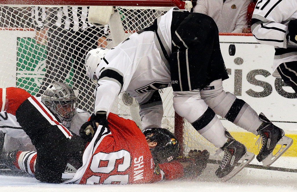. Chicago Blackhawks center Andrew Shaw (65) and Los Angeles Kings center Trevor Lewis (22) collide as Los Angeles Kings goalie Jonathan Quick (32) saves a goal  during the second period in Game 7 of the Western Conference finals in the NHL hockey Stanley Cup playoffs Sunday, June 1, 2014, in Chicago. (AP Photo/Nam Y. Huh)
