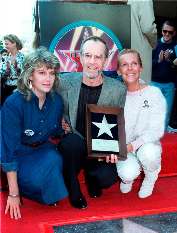 """. ** FILE ** In this Jan. 21, 1987 file photo, comedian George Carlin poses with his daughter Kelly, left, and wife Brenda as he receives a star on the Hollywood Walk of Fame in the Hollywood section of Los Angeles. Carlin, 71, whose staunch defense of free speech in his most famous routine \""""Seven Words You Can Never Say On Television\"""" led to a key Supreme Court ruling on obscenity, died Sunday June 22, 2008. He went into St. John\'s Health Center in Santa Monica on Sunday complaining of chest pain and died later that evening, said his publicist, Jeff Abraham. (AP Photo/Mark Terrill, file)"""