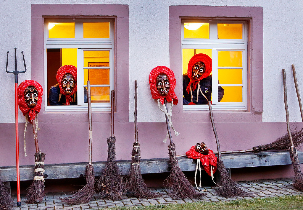 . In this photo taken Saturday, Feb. 25, 2017 witches of the Waldkircher Kandelhexen witches\' club look out of windows as they prepare for celebrating the traditional witches\' sabbath at the market square of Waldkirch, southern Germany, Saturday, Feb. 25, 2017. The members of the Krakeelia carnival club celebrate their annual witches\' sabbath, which takes place on the Saturday before Rose Monday. (AP Photo/Michael Probst)