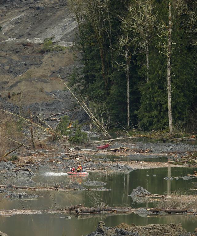 . A search and rescue team navigates the water during operations on March 27, 2014 in Oso, Washington. A massive mudslide killed at least twenty-five and left many missing. (Photo by Ted S. Warren-Pool/Getty Images)