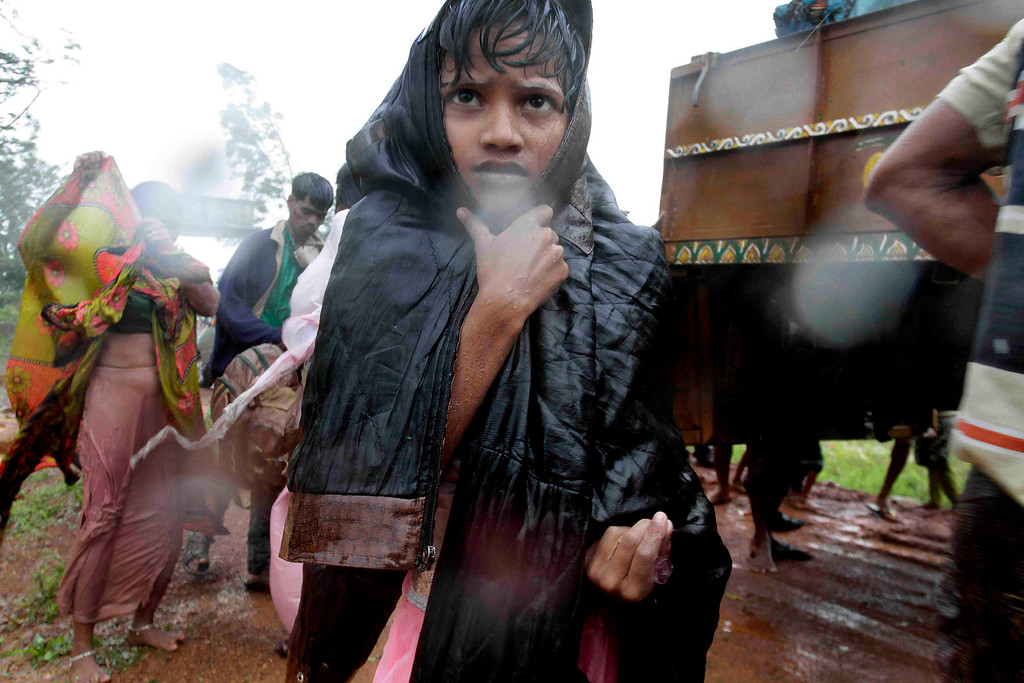 . A younh Indian boy reaches a relief camp after being evacuated as it rains near Berhampur, India, Saturday, Oct. 12, 2013. Hundreds of thousands of people living along India\'s eastern coastline were taking shelter Saturday from a massive, powerful cyclone Phailin that was set to reach land packing destructive winds and heavy rains. (AP Photo/Bikas Das)