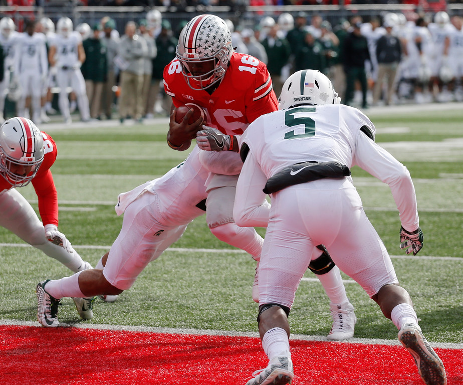 . Ohio State quarterback J.T. Barrett, center, scores a touchdown past Michigan State defenders Khari Willis, left, and Andrew Dowell during the first half of an NCAA college football game Saturday, Nov. 11, 2017, in Columbus, Ohio. (AP Photo/Jay LaPrete)