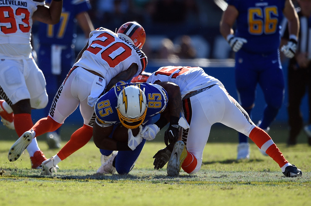 . Los Angeles Chargers tight end Antonio Gates is tackled by Cleveland Browns strong safety Briean Boddy-Calhoun, left, and outside linebacker Christian Kirksey during the first half of an NFL football game Sunday, Dec. 3, 2017, in Carson, Calif. (AP Photo/Kelvin Kuo)