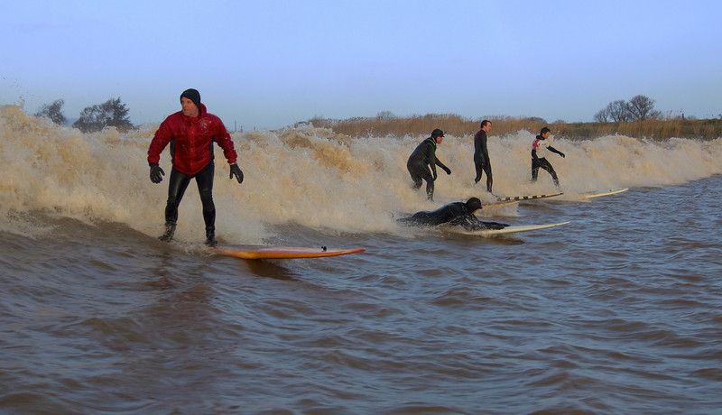 Severn Bore 02 February 2014. All images captured from the river (boat). Having arrived early at the lower part of the river I waited through the sunrise (glorious) as the bore made its ferocious roaring entrance just after 8am. Surfers and crafts waiting patiently until they finally merge as one. Watching, pursuing and moving along and through the chaos as the bore moved inland was a tough old bumpy ride. Photographer and gear soaked/bruised to bits. All images captured with Olympus E-M1, E5 with 50-200mm and 12-50mm lenses.