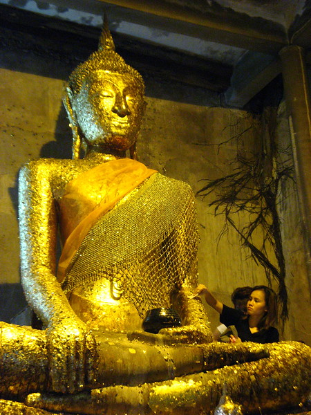 Putting gold leaf on the Buddha image at Wat Bang Goong