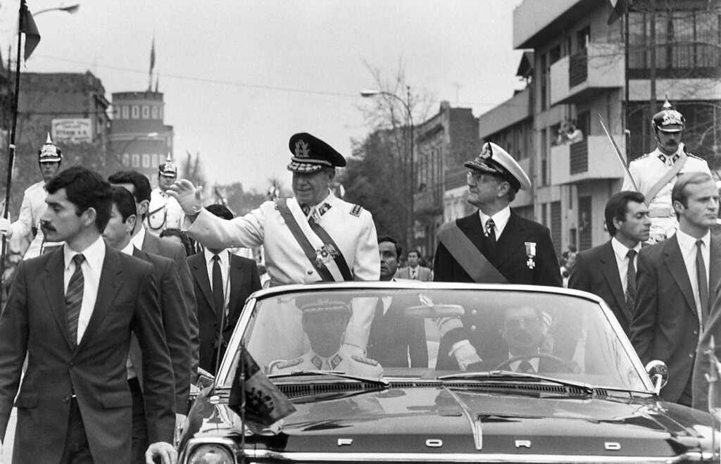 . This undated file photo shows Chilean ruler Gen. Augusto Pinochet (L) waving to well-wishers from a motorcade in Santiago, Chile, while his Defense Minister Vice-Admiral Patricio Carvajal (R) looks on. Pinochet led the 11 September 1973 military coup that toppled and killed leftist president Salvador Allende. AFP PHOTOHO/AFP/Getty Images