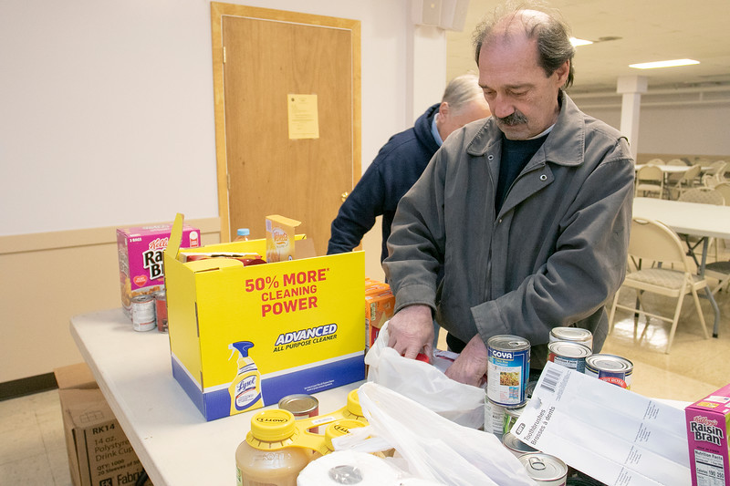 The Knights of Columbus Council 99 on Electric Avenue in Fitchburg held a food drive on Saturday, March 21, 2020. They brought the food they collected to St. Francis of Assisi, on Sheridan Street in Fitchburg, who have had a food pantry on Friday's from 12 p.m. to 2 p.m. Their food pantry at the church has been around for over 40 years. Sorting through the food is Dan Cucchiara KoC Grand Knight. SENTINEL & ENTERPRISE/JOHN LIOVE