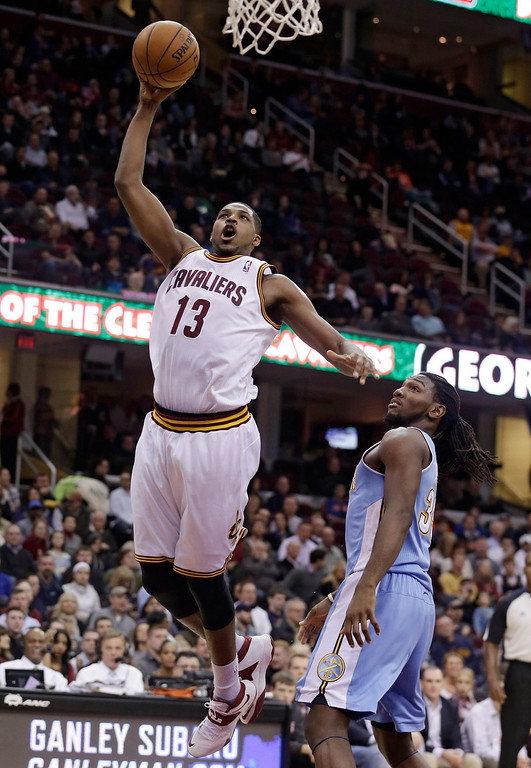 . Cleveland Cavaliers\' Tristan Thompson (13), from Canada, jumps to the basket against Denver Nuggets\' Kenneth Faried (35) during the second quarter of an NBA basketball game on Wednesday, Dec. 4, 2013, in Cleveland. (AP Photo/Tony Dejak)