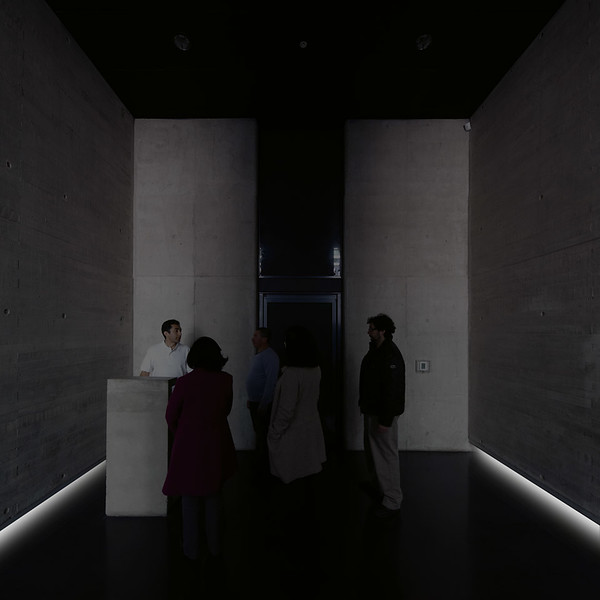 A docent trained by Alfredo Jaar provides information about the imminent memorial experience, and guides them into the enclosed inner chamber. (Courtesy Alfredo Jaar Studio)