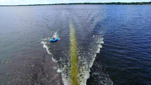 Aerial of woman tubing behind boat on lake in summer