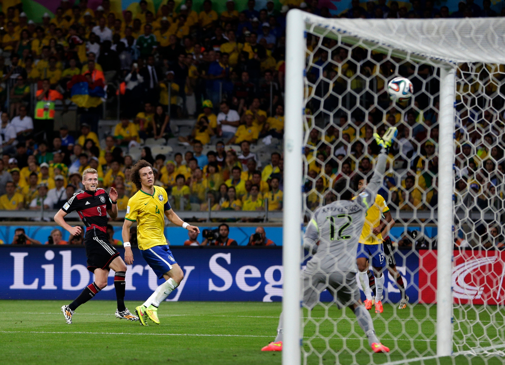 Description of . Germany's Andre Schuerrle, left, scores his side's seventh goal during the World Cup semifinal soccer match between Brazil and Germany at the Mineirao Stadium in Belo Horizonte, Brazil, Tuesday, July 8, 2014. (AP Photo/Matthias Schrader)